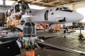 Repair of an AN-26 cargo plane in a hangar. Screw in the foreground Wall mural