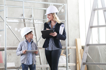 woman interior designer or architect mom with her son they work together on the construction of the house, inside the building site