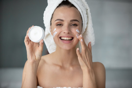 Smiling young woman in towel after shower use recommend moisturizing facial cream or mask, excited millennial lady apply face beauty product for healthy glowing skin, skincare concept