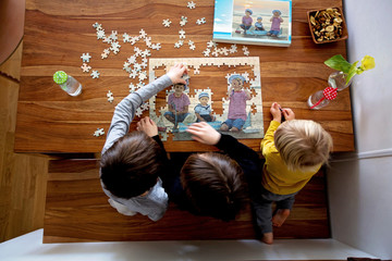 Three children, boys, assembling puzzle with their picture from the beach, playing at home