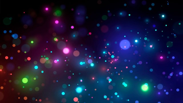 Glowing neon drops of paint on a dark background or blurry colorful sparks