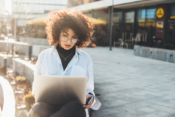 Businesswoman with curly hair and eyeglasses working outside with a laptop in a sunny day