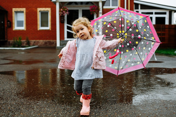 Cute little blonde girl in pink jacket, gray pants and rubber boots is jumping over a puddle on a rainy day Fotobehang