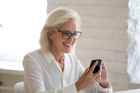 Close up happy attractive 60 years old businesswoman using smartphone and getting good news. Smiling mature woman user using mobile modern technology for online business chat.