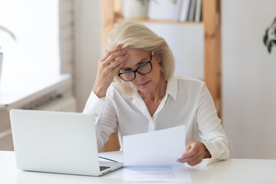 60 years old serious businesswoman reading document holding ache at work. Tired woman employee looking at report on paper near modern laptop having headache. Stressful business deal concept.