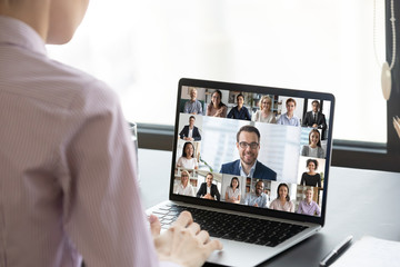 Multiracial people involved in group video call using modern tech videoconferencing application for study or business concept, view over businesswoman shoulder sitting at desk working with colleagues