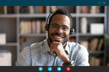 Head shot African man wear headset sit at desk look at cam use videocall conferencing app, pc screen view. Company consultant, teacher portrait, easy e-learn, distant communication with client concept Fotobehang