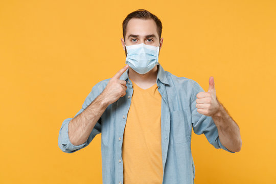 Young man in casual clothes posing isolated on yellow background. Epidemic pandemic coronavirus 2019-ncov sars covid-19 flu virus concept. Pointing index finger on sterile face mask, showing thumb up.