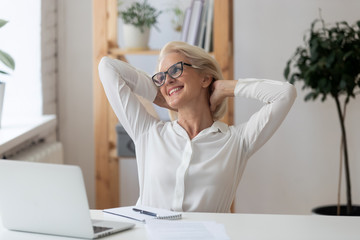 Satisfied 60 years old businesswoman with hands behind head relaxing in comfortable office chair during break. Smiling female employee resting after work done, leaning back, daydreaming. Fotomurales