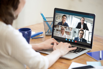 Diverse people take part in group video call pc screen cam app view over woman shoulder, seated at...