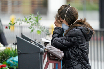 Adriana Gomez prays outside the Our Lady Queen of Angels Catholic Church on Palm Sunday during the outbreak of the coronavirus disease (COVID-19) in Los Angeles, California