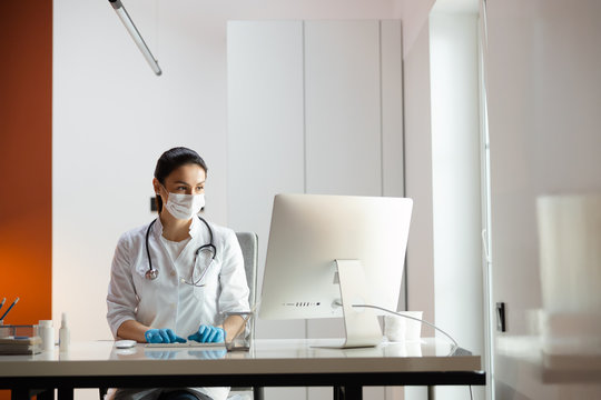 Caucasian doctor in medical mask and rubber gloves working at laptop