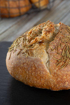A view of a rustic sourdough boule loaf featuring rosemary, in a restaurant or kitchen setting.