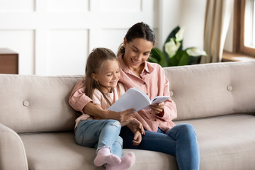 Attractive young mixed race woman nanny cuddling little kid, reading paper book together on comfortable sofa in living room. Happy mother educating small child daughter, enjoying weekend time at home.