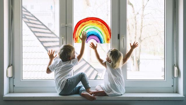 Little children on background of painting rainbow on window