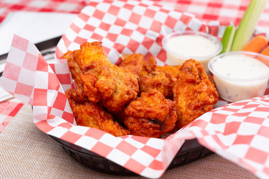 A view of a basket of buffalo wings in a restaurant or kitchen setting.