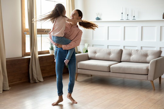 Smiling young barefoot mixed race woman holding on hands little adopted kid girl, twisting together in living room. Happy mommy dancing to music, having fun with excited small daughter at home.