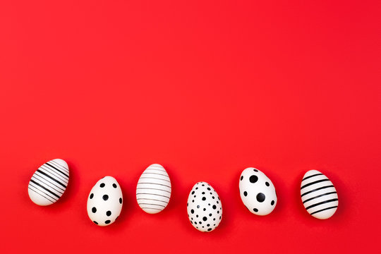 Different graphic hand-painted eggs on trendy coral background. Easter concept. Place for text.