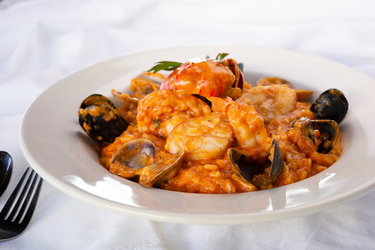 A view of a bowl of seafood risotto, in a restaurant or kitchen setting.