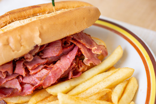 A closeup view of a pastrami sandwich and french fries, in a restaurant or kitchen setting.