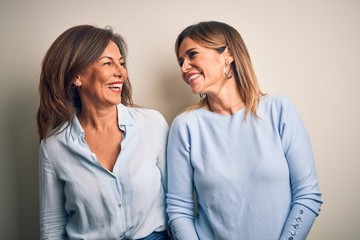 Wall Mural - Middle age beautiful couple of sisters standing over isolated white background looking away to side with smile on face, natural expression. Laughing confident.