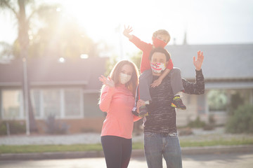 Family in face masks standing in the neighborhoods, waving, greeting. Many countries recommend citizens cover their faces during the world coronavirus covid-19 pandemic. Wall mural