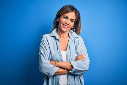 Middle age beautiful woman wearing casual shirt standing over isolated blue background happy face smiling with crossed arms looking at the camera. Positive person.