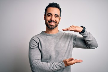 Young handsome man with beard wearing casual sweater standing over white background gesturing with hands showing big and large size sign, measure symbol. Smiling looking at the camera. Measuring Wall mural