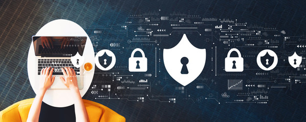 Wall Mural - Cyber security theme with person using a laptop on a white table