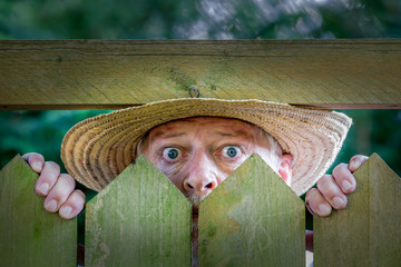 An elderly man in a straw hat looks curiously over a garden fence. Concept: curiosity and neighborhood