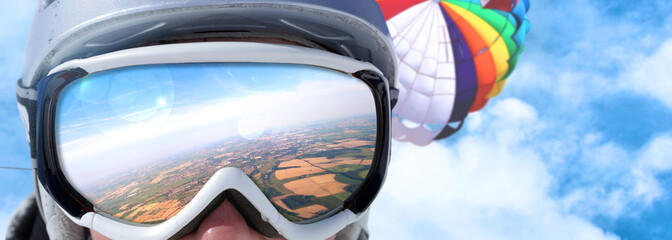 Goggles of a skydiver reflecting the landscape scenery below