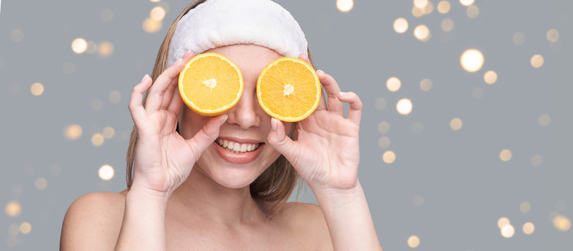 Girl hold orange slice. Citrus fruit hidding face. antioxidant home care routine. Facial energy product. Laughing portrait. Modern nature cosmetic. Ecology beauty. Copyspace with bokeh lights
