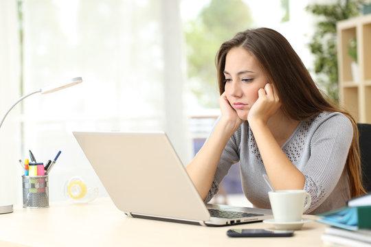 Bored entrepreneur looking at laptop screen at home