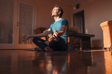 Handsome man practicing yoga in his living room, he feel peaceful and enjoying in moments