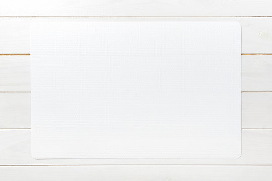 Top view of empty white tablecloth on wooden background with copy space