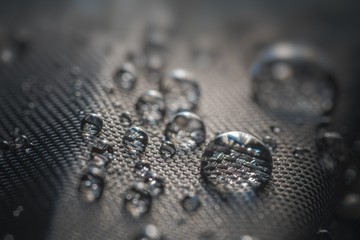 Many water drops on waterproof impregnated fabric of black umbrella.