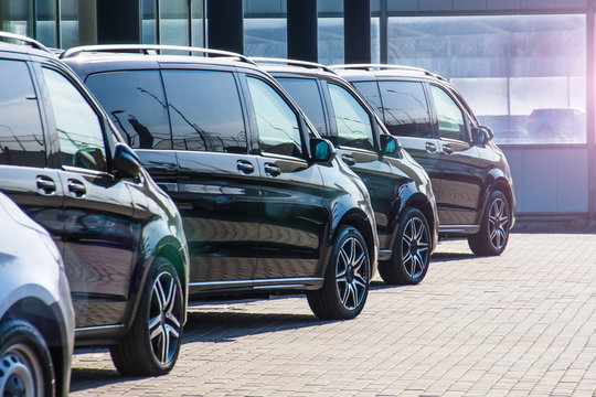 Dark colored passenger vans in a parking lot.