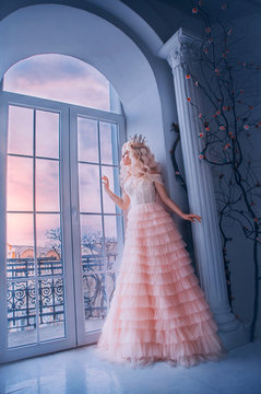 Fantasy beautiful medieval woman princess stands near window castle white room. Girl looking outdoor with hope . Pink long luxury dress. Lady queen wavy blonde hair. Vintage royal crown. Stay home
