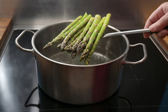 Hand puts green asparagus on a skimmer in a pot with boiling water for a holiday dinner, healthy cooking concept, copy space