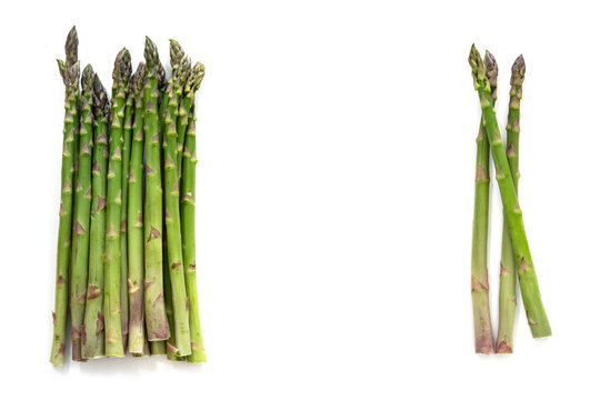 Two bunches of organic green asparagus (Asparagus officinalis) and copy space in the middle,  isolated with small shadows on a white background, high angle view from above
