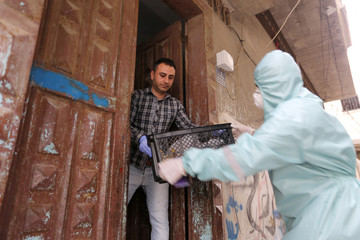 A Palestinian man at his home receives from a delivery worker a crate containing sanitized vegetables, in the central Gaza Strip