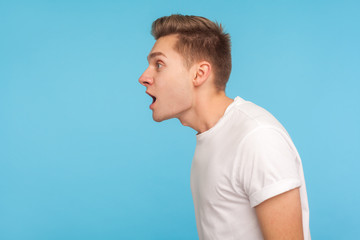 Wow, amazing! Side view of astonished man in casual white t-shirt standing with mouth open in surprise, scared and shocked by crazy unbelievable news. indoor studio shot isolated on blue background