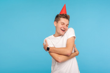 Happy birthday to me! Funny positive man with party cone on head, embracing himself with expression of pleasure, happy to celebrate holiday alone, self-love concept. studio shot blue background