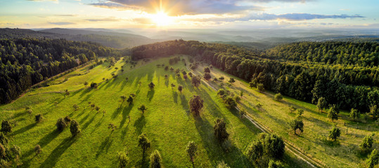 Aerial landscape panorama after sunrise: gorgeous scenery with the sun, trees on meadows casting long shadows, surrounded by forests Fototapete