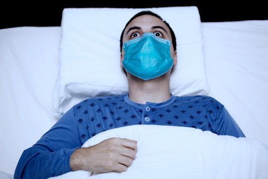 Portrait of an insomniac man trying to sleep while wearing a mask, coronavirus quarantine concept