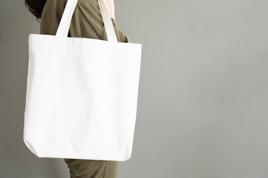 Blank white tote bag canvas fabric with handle mock up design. Close up of woman holding eco or reusable shopping bag near grey wall. No plastic bag and ecology concept. Copy space.