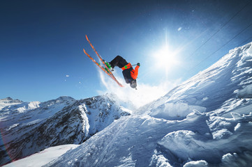 Low angle view athlete skier in an orange jacket does a back flip with flying powder of snow against a clear blue sky sun and snow-capped mountains of the Caucasus.