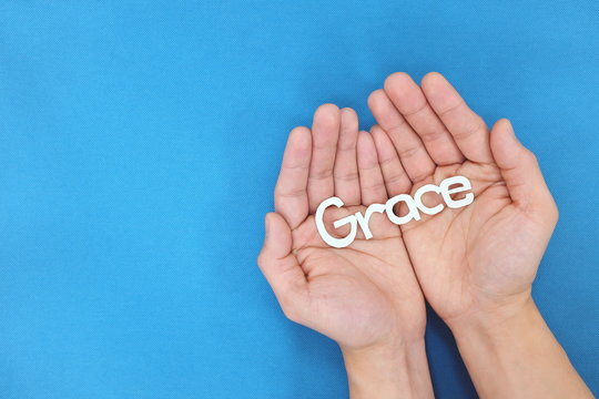 Male hands praying for grace from God in blue background. Top view with copy space.