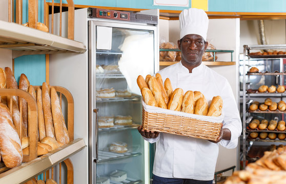 African American baker holding baguettes