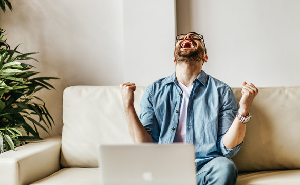 Excited male businessman celebrating victory, success, triumph  while working at laptop